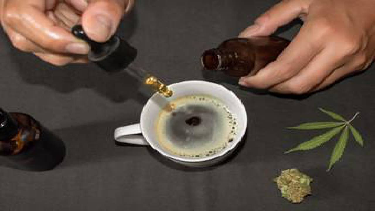 A person adding CBD oil to their coffee