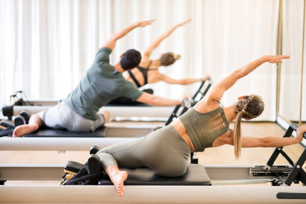 three people performing a Pilates exercise on Reformers