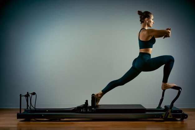 woman performing a Pilates exercise on a Reformer